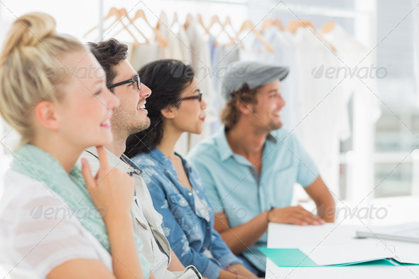 Group of fashion designers discussing designs in a studio - Stock Photo - Images