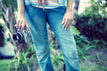 Woman wearing jeans holding camera outside on a sunny day - PhotoDune Item for Sale