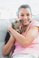 Pretty woman cuddling her yorkshire terrier on the couch at home in the living room
