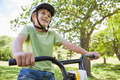 Low angle view of a smiling young boy riding bicycle at the park