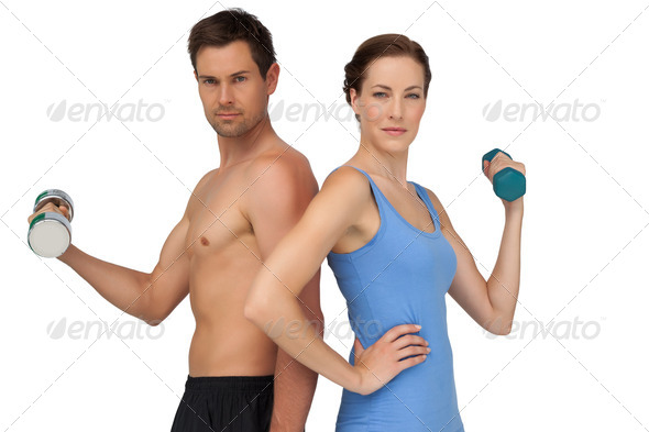 Fit young couple exercising with dumbbells over white background - Stock Photo - Images