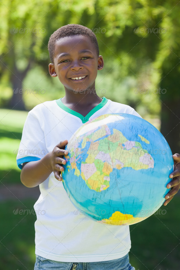 Little boy smiling at camera holding globe in the park on a sunny day - Stock Photo - Images