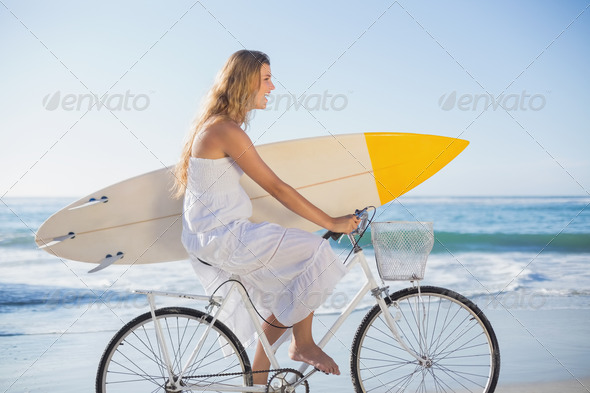 Beautiful surfer in sundress on bike holding surfboard at the beach on a sunny day - Stock Photo - Images
