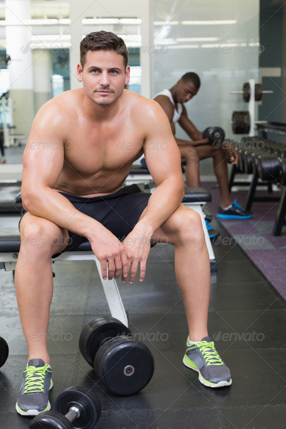 Handsome bodybuilder sitting on bench in weights room at the gym - Stock Photo - Images