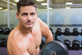 Handsome bodybuilder lifting heavy dumbbell at the gym