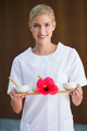 Smiling beauty therapist holding tray of treatments at the spa - PhotoDune Item for Sale