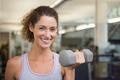 Fit woman smiling at camera lifting dumbbell at the gym