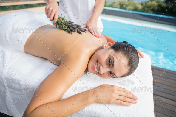 Smiling woman getting an aromatherapy treatment poolside outside at the spa - Stock Photo - Images