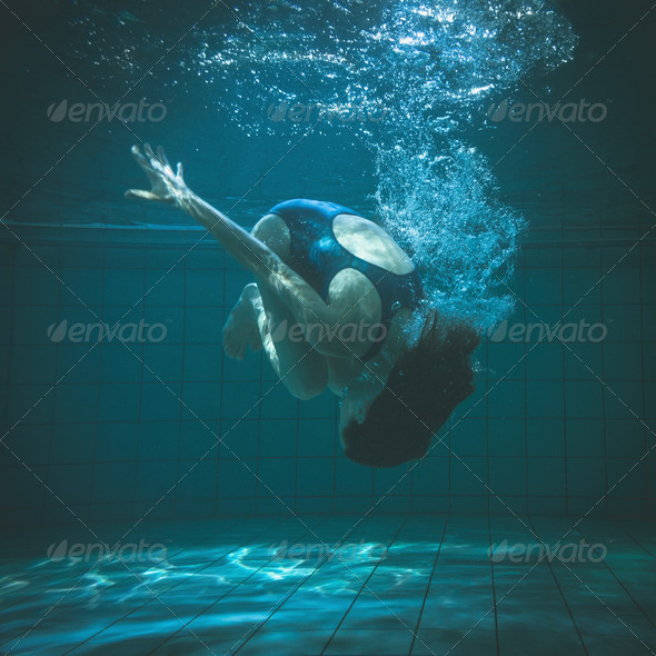 Athletic swimmer doing a somersault underwater in the swimming pool at the leisure centre - Stock Photo - Images