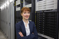 Pretty technician smiling at camera beside server tower in large data center - PhotoDune Item for Sale