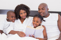 Happy family reading book together in bed at home in the bedroom