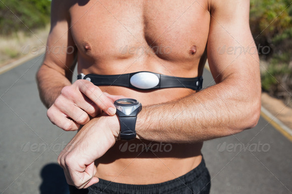 Athletic man on open road with monitor around chest on a sunny day - Stock Photo - Images