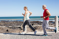 Fit mature couple jogging together on the pier on a sunny day