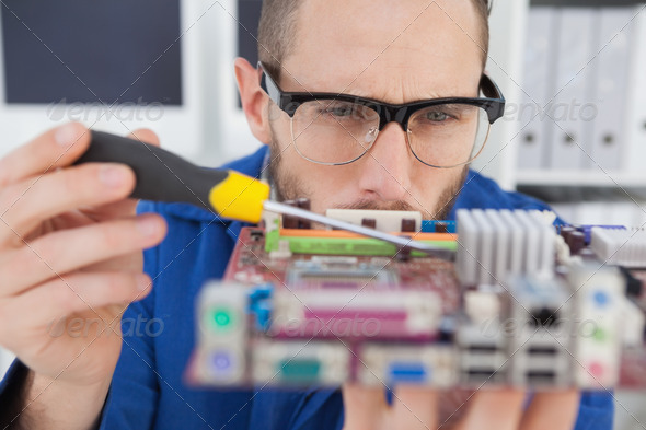 Computer engineer working on cpu with screwdriver in his office - Stock Photo - Images