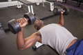 Young muscular man exercising with dumbbells in gym - PhotoDune Item for Sale