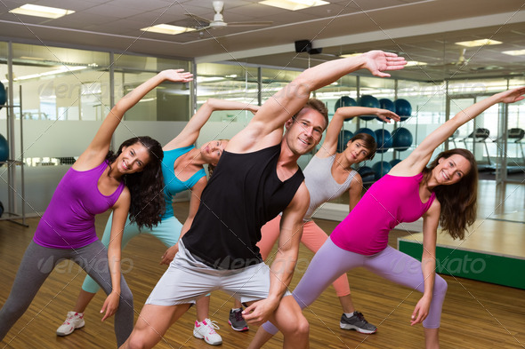 Fitness class led by handsome instructor at the gym - Stock Photo - Images