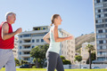 Fit mature couple jogging together on a sunny day