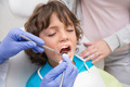 Pediatric dentist examining a little boys teeth with his mother at the dental clinic - PhotoDune Item for Sale
