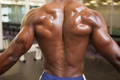 Rear view of a shirtless bodybuilder standing in gym