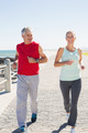 Fit mature couple jogging on the pier on a sunny day