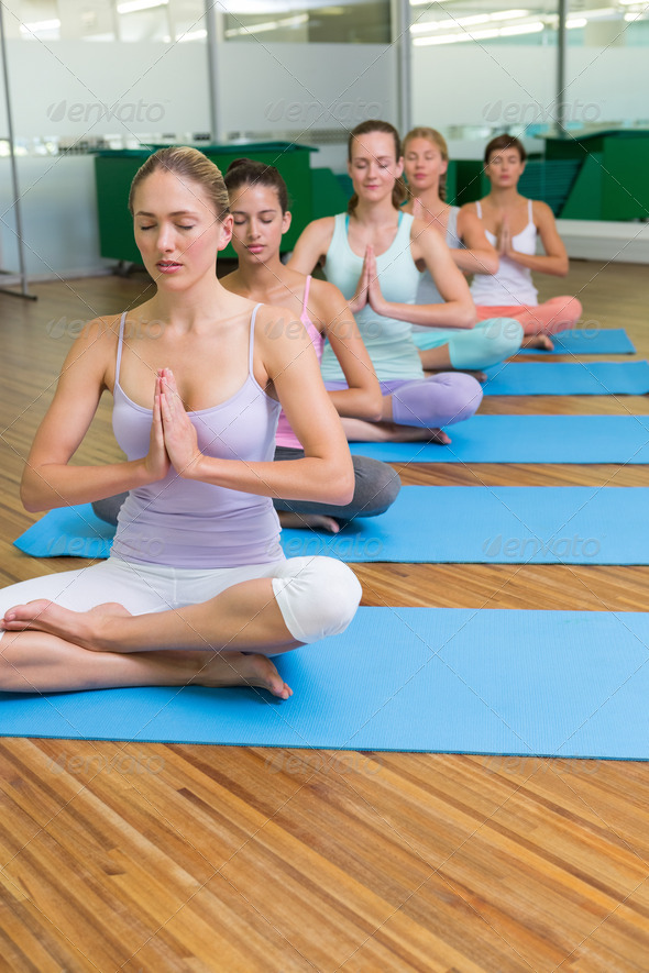 Yoga class in lotus pose in fitness studio at the leisure center - Stock Photo - Images