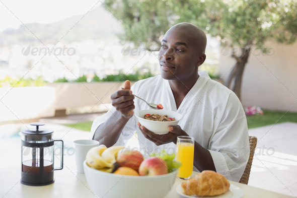 Handsome man in bathrobe having breakfast outside on a sunny day - Stock Photo - Images