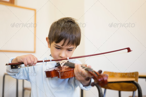 Cute pupil playing violin in classroom at the elementary school - Stock Photo - Images