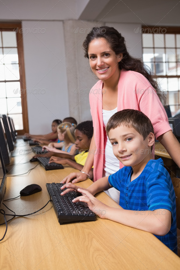 Cute pupils in computer class with teacher at the elementary school - Stock Photo - Images