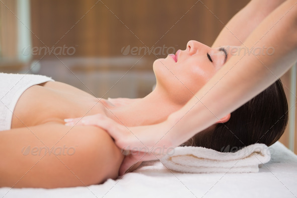 Side view of an attractive young woman receiving shoulder massage at spa center - Stock Photo - Images