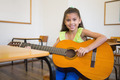 Cute pupil playing guitar in classroom at the elementary school - PhotoDune Item for Sale