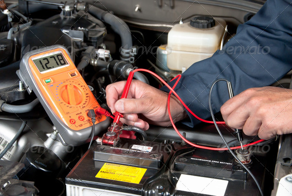 Auto mechanic checking car battery voltage - Stock Photo - Images