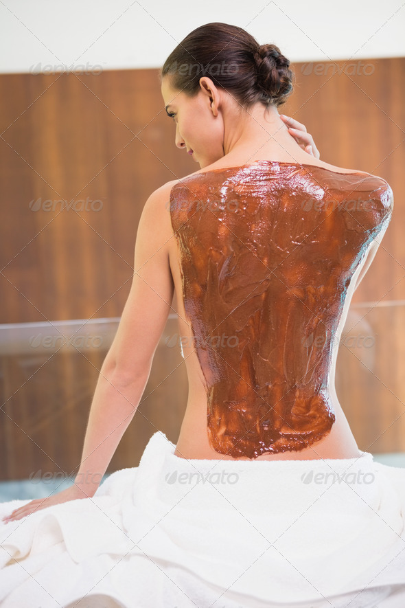 Rear view of an attractive young woman with chocolate back mask at spa center - Stock Photo - Images