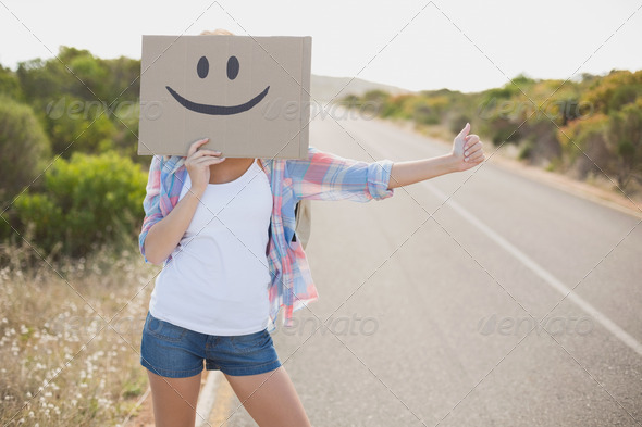 Portrait of a woman with smiley face hitchhiking on countryside road - Stock Photo - Images
