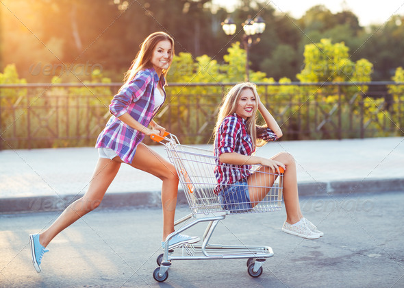 Two happy beautiful teen girls driving shopping cart outdoors - Stock Photo - Images