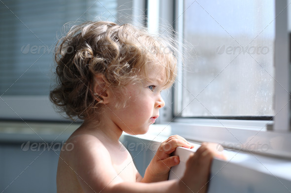 Child looking into window - Stock Photo - Images