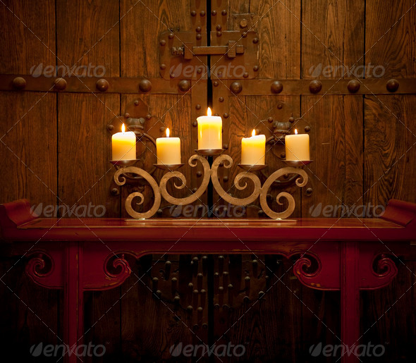 Candles burning on table in front of old rustic door - Stock Photo - Images