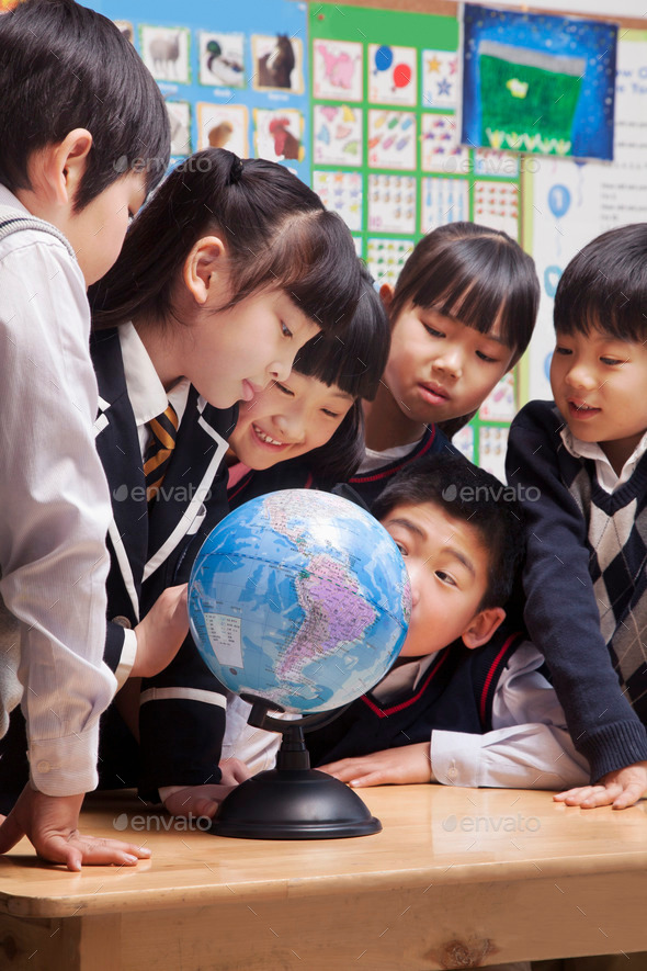 Schoolchildren looking at a globe in the classroom - Stock Photo - Images
