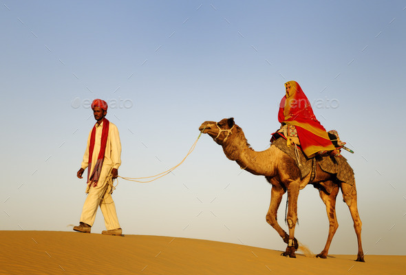 Indigenous Indian Man And Woman Traveling Through The Desert Rid - Stock Photo - Images