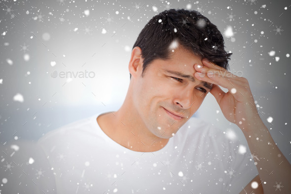 Worried man having a headache sitting in his bedroom against snow falling - Stock Photo - Images