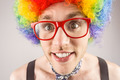 Geeky hipster in afro rainbow wig on grey background