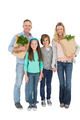 Smiling family standing holding bag of healthy groceries on white background