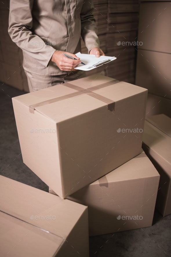 Close up mid section of warehouse worker with clipboard in warehouse - Stock Photo - Images