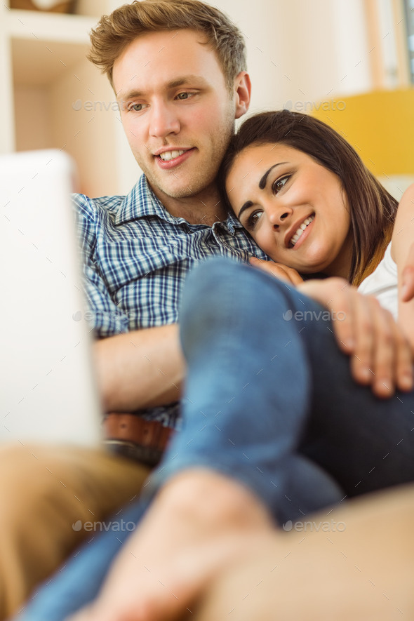 Happy young couple relaxing on the couch with laptop at home in the living room - Stock Photo - Images