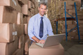 Portrait of warehouse manager using laptop at warehouse - PhotoDune Item for Sale