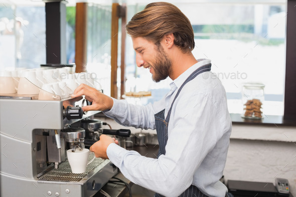 Handsome barista making a cup of coffee at the coffee shop - Stock Photo - Images