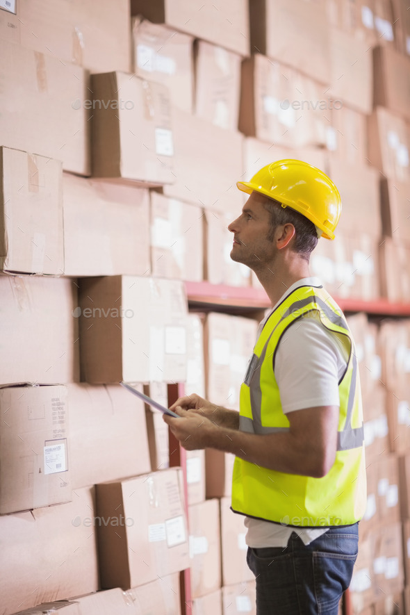 Warehoue worker using digital tablet in warehouse - Stock Photo - Images