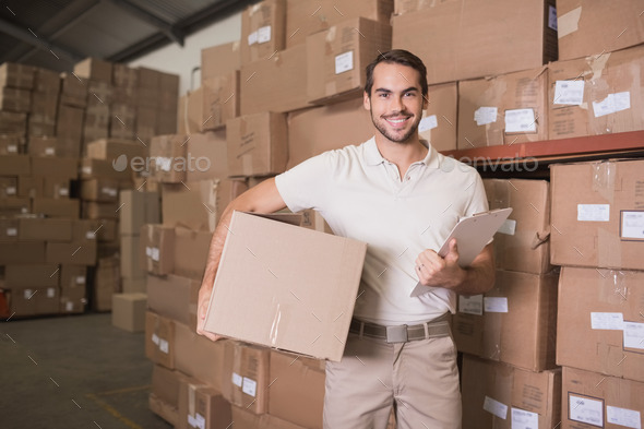 Portrait of smiling delivery man with box and clipboard in warehouse - Stock Photo - Images