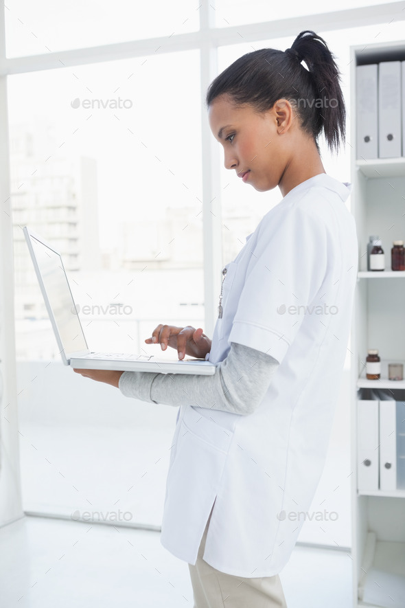 Doctor using her laptop in her office - Stock Photo - Images