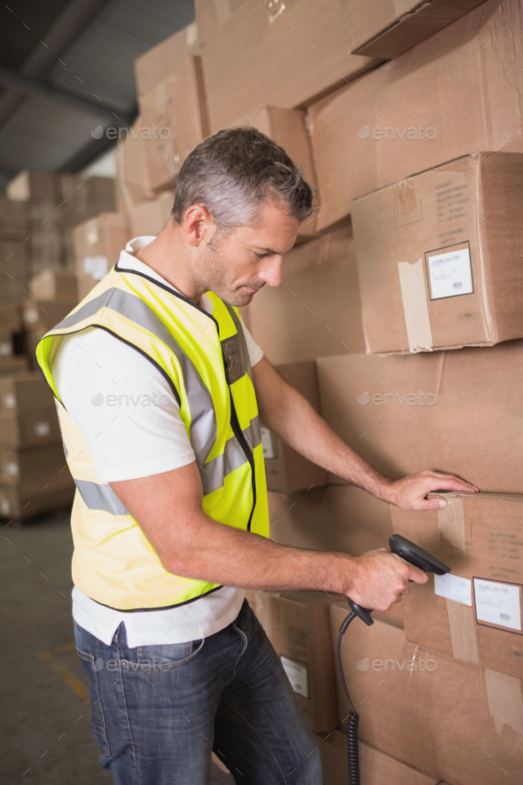 Side view of manual worker scanning package in the warehouse - Stock Photo - Images