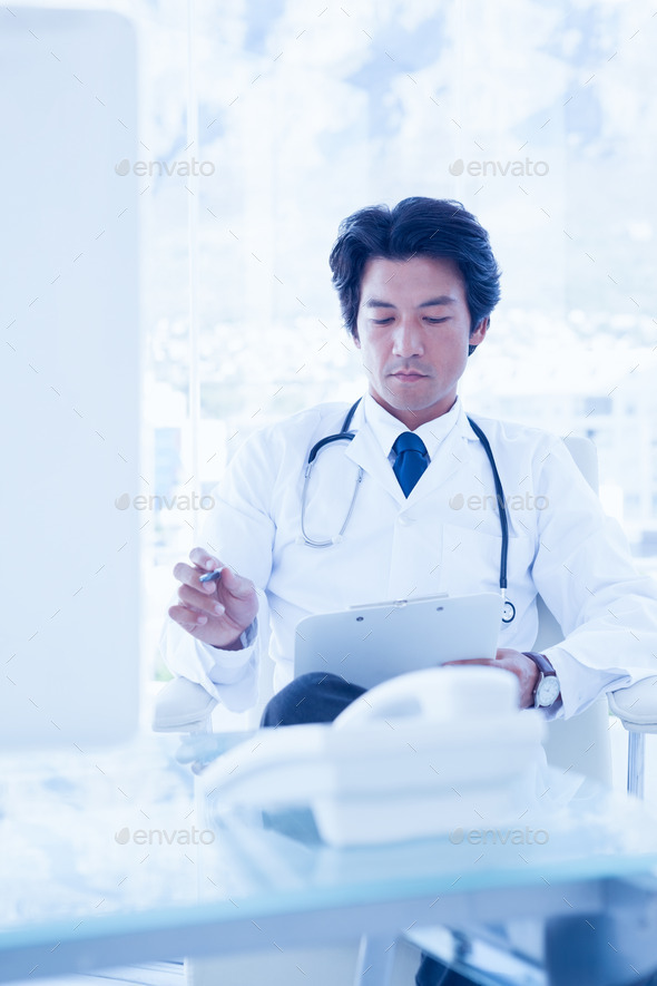 Focused doctor reading over notes in his office - Stock Photo - Images